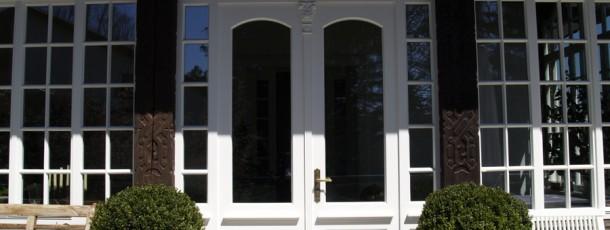 Manufakturfenster Terassentür und geschnitzte Säulen mit Drachenköpfen